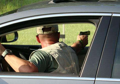 man in car with gun